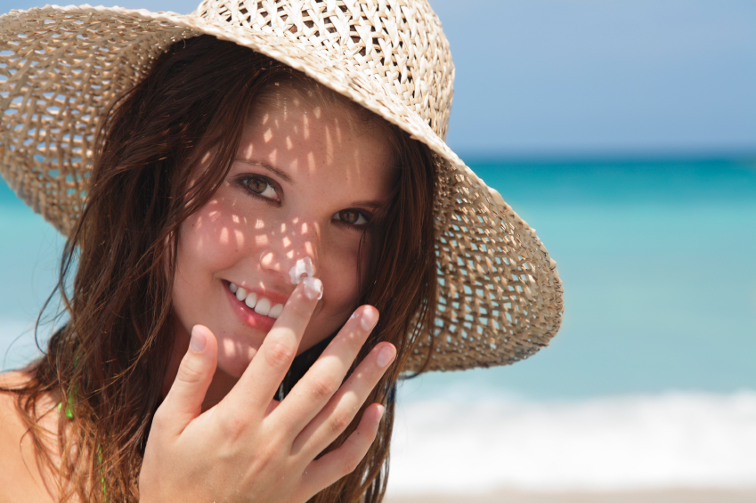 young lady applying sunscreen at the beach